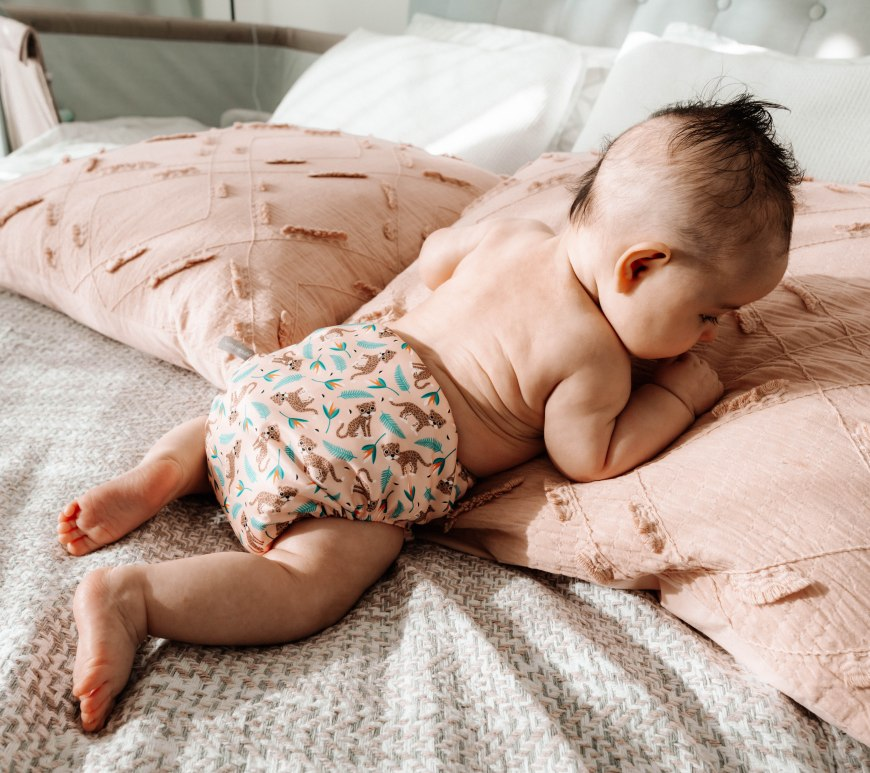 baby in nappy crawling on bed